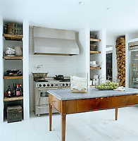 The kitchen island is a large marble-topped antique table and behind it is a large stainless-steel English range and extractor hood