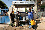 Palestinian children fill plastic bottles and jerry cans with drinking water from a public tap marking the Water World Day in Beit Lahia in the northern Gaza Strip, on March 22, 2016. Photo by Ashraf Amra