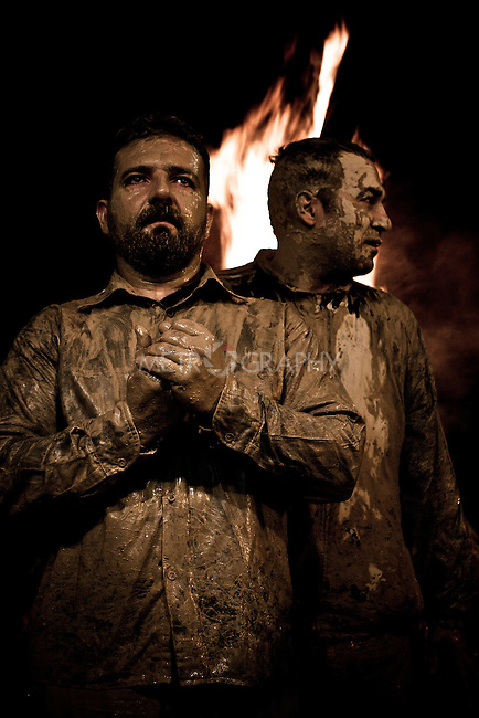 KHORRAMABAD, IRAN : Men dry their muddy bodies next to a fire during the festival of Ashura...Every year to mark the death of Imam Hussein, Shia Muslims mourn for two days. In Khorramabad and Lorestan in the west of Iran, during the first day of mourning, called Tasooa, women take a vow of silence and go through the streets with the children lighting candles. At 4 am on Ashura, the second day, men cover themselves in mud and then stand in front of a fire until the mud has dried to clay. After this they go to the mosque and pray...Photo by Farhad Babaei/Metrography