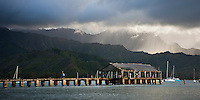 Rain showers pass by Kauai's iconic Hanalei Bay, with Hanalei pier in the foreground. Sailboats are anchored seasonally during the calm summer months.