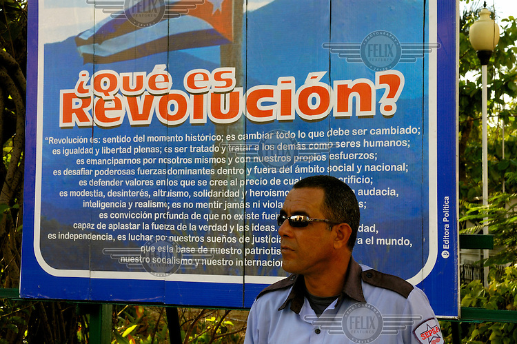 A SEPSA security guard wearing sunglasses guards his post in front of a propaganda poster quoting President Fidel Castro - 'What is Revolution?'