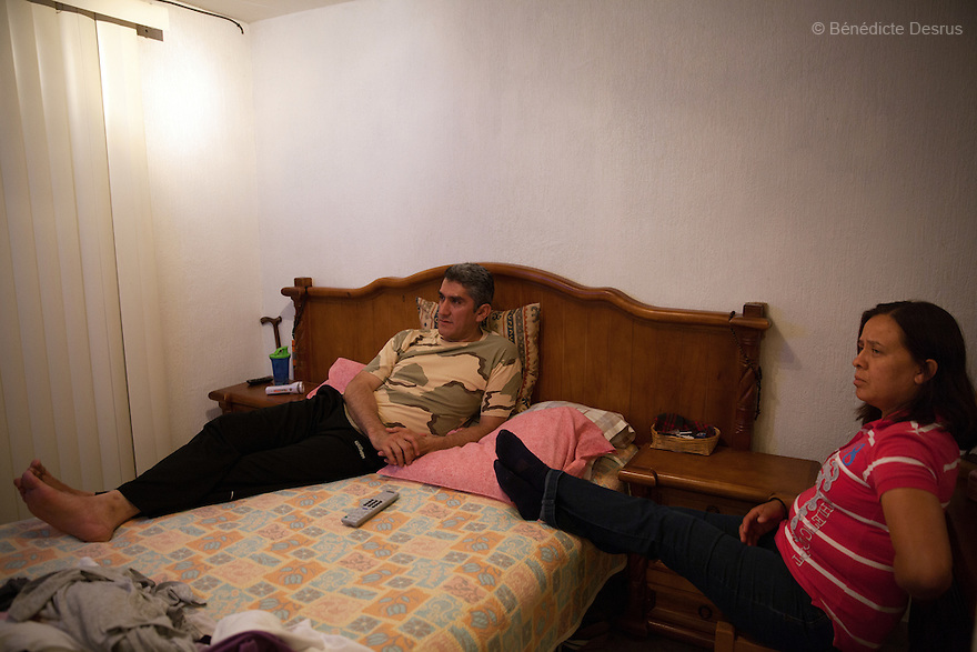 """Donovan watches television with his wife in their bedroom at home in Texcoco, Mexico on May 21, 2015. Donovan Tavera, 43, is the director of """"Limpieza Forense México"""", the country's first and so far the only government-accredited forensic cleaning company. Since 2000, Tavera, a self-taught forensic technician, and his family have offered services to clean up homicides, unattended death, suicides, the homes of compulsive hoarders and houses destroyed by fire or flooding. Despite rising violence that has left 70,000 people dead and 23,000 disappeared since 2006, Mexico has only one certified forensic cleaner. As a consequence, the biological hazards associated with crime scenes are going unchecked all around the country. Photo by Bénédicte Desrus"""