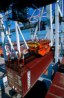Aerial view of a huge dock crane as it lifts containerized freight.