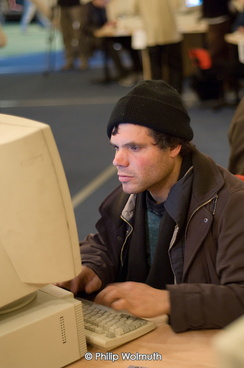 A homeless 'guest' uses a computer to access the internet in the IT suite at the Crisis Open Christmas shelter in the London Arena, Docklands.