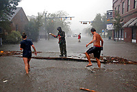 People survey the damage caused by Hurricane Florence on Front Street in downtown New Bern, N.C., on Friday, Sept. 14, 2018. (AP Photo/Chris Seward)