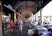 Mantova, Via Broletto, gente seduta ai tavolini di un bar sotto i portici.<br /> Mantua, Via Broletto, People sitting at an outdoor cafe in the arcades.