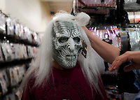 "NWA Democrat-Gazette/CHARLIE KAIJO David Townsend of Rogers (center) tries on a Halloween mask as Carolyn Monroe (right) helps him, Monday, October 8, 2018 at the Halloween Express store in Rogers. ""WeÕre just like kids. We enjoy it too,"" he said about shopping for Halloween costumes. ""Probably enjoy it more than the kids do."""