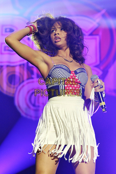 Alexis Jordan.Performing live at the 'Girlguiding UK  Big Gig' at Wembley Arena, London, UK, 1st October 2011..music concert  denim red polka dot stripes half length live on stage arm raised up  white fringed skirt bustier top  hand on head hair armpit .CAP/MAR.© Martin Harris/Capital Pictures.