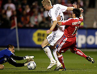 Real Salt Lake goalkeeper Nick Rimando (18) makes the save as defender Nat Borchers (6) shields Chicago Fire midfielder John Thorrington (11) from the ball.  Real Salt Lake defeated the Chicago Fire in a penalty kick shootout 0-0 (5-4 PK) in the Eastern Conference Final at Toyota Park in Bridgeview, IL on November 14, 2009.