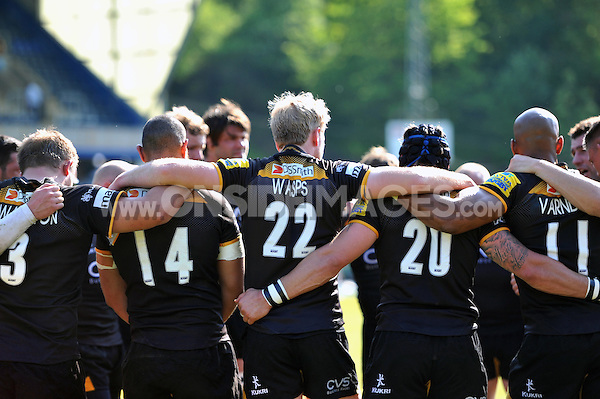 Wasps players huddle together after the match. European Champions Cup play-off, between London Wasps and Stade Francais on May 18, 2014 at Adams Park in High Wycombe, England. Photo by: Patrick Khachfe / JMP