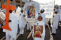 Eritrea. Asmara. September square. Meskel is the most important religious feast for the orthodox church in Eritrea. It takes place every year on september 27. Children (boys and girls) are dressed in white cotton loinclothes and wear a holy cross on their foreheads. A couple of young boys carry a frame, decorated with a shiny plastic flower paper. The frame shows a painting of the Queen of Peace, the Virgin Mary as the Holy Mother holding her son Jesus in her arms. The Virgin Mary  and Jesus have both a golden crown on their heads.  A boy carries a picture of Jesus adult while another holds in his hands an orange cross made out od cardboard. © 2002 Didier Ruef