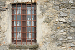 A window with lace curtains illustrated with people in Victorian costumes on them, in a town just above Gravedona on Lake Como, Italy.