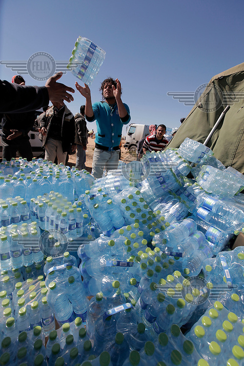 Drinking water is unloaded at a refugee camp near the border with Libya. Tens of thousands of people, mainly Egyptian workers, fled unrest in Libya and crossed the border into Tunisia. Some slept in the open for several days before being processed.  At the same time forces loyal to Col. Gaddafi fought opposition forces in various parts of the country.
