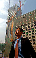 A businessman is walking in the SOHO area in Beijing, China. SOHO area is a new development of small offices, meant to attract small businesses in the Central Business District (CBD)..16 Sep 05