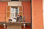 A man reads the newspaper on his balcony in the small mountain town of Naggio, in the mountains above Lake Como, Italy