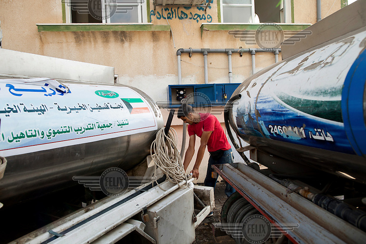 A man fills water trucks at the Al-Maghazi Desalination Plant. The plant provides drinking water free of charge to local hospitals, schools and mosques and members of the community most in need.