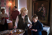 NWA Democrat-Gazette/CHARLIE KAIJO Former board member and long time volunteer of Washco Historical Society Dee Dee Lamb serves Malachi Cross, 8, of Springdale (from left) during the Washco Historical Society annual Holiday Open House, Sunday, December 2, 2018 at the Headquarters House in Fayetteville.<br /><br />Visitors enjoyed treats and drinks and carolers sang for neighbors of the Headquarters House.