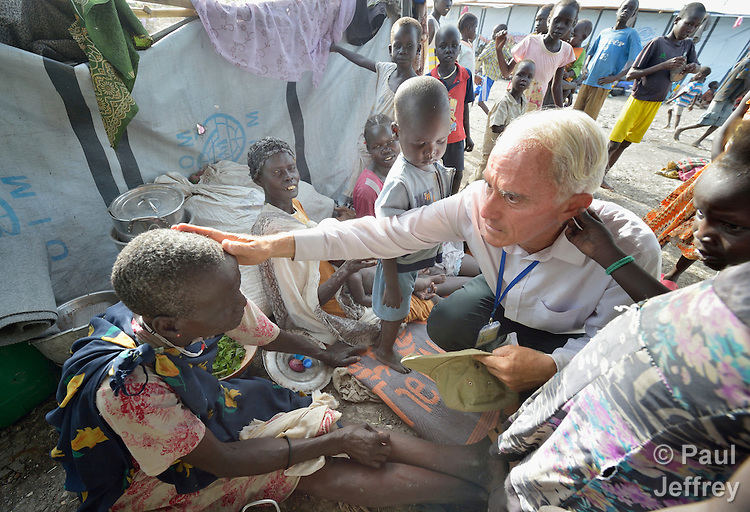 Father Mike Bassano, a Maryknoll priest from the United States, blesses a displaced woman inside a United Nations base in Malakal, South Sudan. More than 20,000 civilians have lived inside the base since shortly after the country's civil war broke out in December, 2013, but renewed fighting in 2015 drove another 5,000 people, including this woman, into the relative safety of the camp. Bassano lives in the camp to accompany the people there.