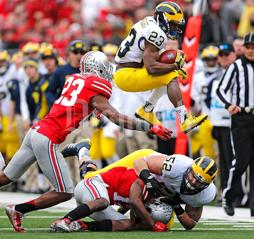 Michigan Wolverines wide receiver Dennis Norfleet (23) leaps past Ohio State Buckeyes safety Tyvis Powell (23) during the second quarter of the NCAA football game against Michigan at Ohio Stadium on Saturday, November 29, 2014. (Columbus Dispatch photo by Jonathan Quilter)