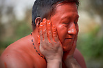 A man paints his face with urucum before a march by indigenous people through the streets of Atalaia do Norte in Brazil's Amazon region on March 27, 2019. They were protesting a central government plan to turn control of health care over to municipalities, in effect destroying a federal program of indigenous health care. Indian rights activists are worried that the government of President Jair Bolsonaro is reducing or eliminating protections for the country's indigenous people.