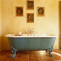 A blue-grey roll top bath stands on the terracotta tiled floor in the bathroom