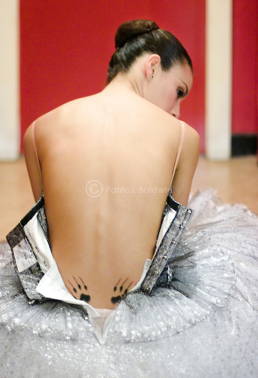 Principal dancer with English National Ballet Fernanda Oliveira backstage with her tutu undone revealing her claw tattoo on her lower back