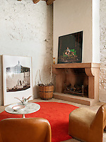 Retro furniture and contemporary photography grouped in front of the large original fireplace in the sitting room