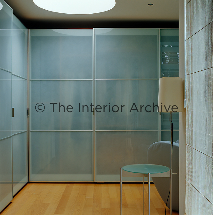Glass sliding doors cover the wall-to-wall wardrobes in this dressing room