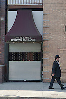 An Hasidic Jewish men walks by the Ladies entrance of a temple in the Borough Park section of the the New York City borough of Brooklyn, NY, Monday August 1, 2011. Borough Park is home to one of the largest Orthodox Jewish communities outside of Israel, with one of the largest concentrations of Jews in the United States and Orthodox traditions, rivaling many insular communities.