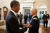 United States President Barack Obama presents White House Military Aide Lieutenant Colonel Barrett Bernard, U.S. Army, with the Defense Superior Service Medal during a departure ceremony in the Oval Office, October 12, 2011. Additional military aides stand at attention in the background. .Mandatory Credit: Chuck Kennedy - White House via CNP