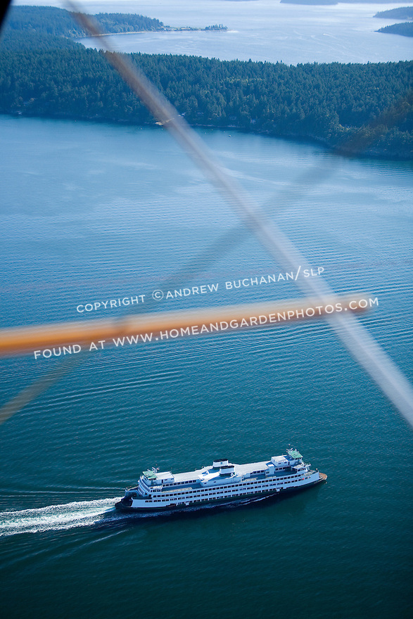 A lone, white Washington State car ferry plows determinedly forward through the deep blue green summer waters of the San Juan Islands as seen from the air through the wire cross braces of a classic biplane.