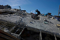 Port au Prince, Haiti, Jan 16 2010.Many people search the ruins for personal belongings.