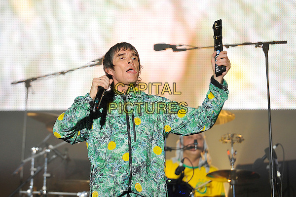 Ian Brown of The Stone Roses.performing at V Festival, Hylands Park, Chelmsford, Essex, England. .18th August 2012.on stage in concert live gig performance music half length green yellow grey gray jacket yellow print  singing mouth open tongue tambourine .CAP/MAR.© Martin Harris/Capital Pictures.