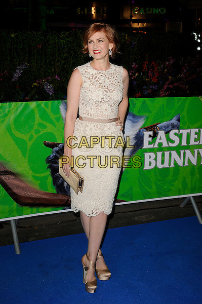 Isla Fisher.Attending the UK Premiere of 'Rise Of The Guardians', Empire Cinema, Leicester Square, London, England, UK. 15th November 2012..full length sleeveless white cream lace peplum dress clutch bag gold silk satin beige ribbon waistband hand on hip shoes .CAP/MAR.© Martin Harris/Capital Pictures.