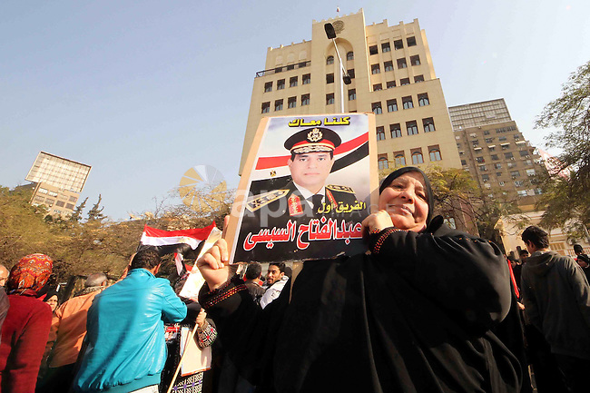 An Egyptian woman holds a poster of Abdel Fattah el-Sisi, Egypt's Minister of Defense, during a demonstrations in front of the Qatari embassy to demand Egypt sever diplomatic ties with the State of Qatar, in Giza's Dokki district, Cairo, January 07, 2014. The Egyptian Ministry of Foreign Affairs has summoned Qatar's ambassador to Egypt to protest Doha's interference in Egyptian internal affairs after Doha's criticism of Egypt's crackdown on Morsi's Muslim Brotherhood on Saturday. Photo by Mohammed Bendari