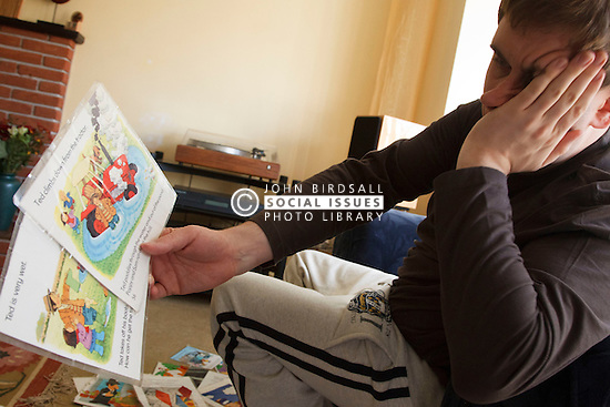 Young man with autism looking at pages from children's books. Cleared for Mental Health issues.