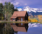 Cabin and peak reflected in pond, near Telluride at Skyline Ranch, Rocky Mountains, Colorado, USA