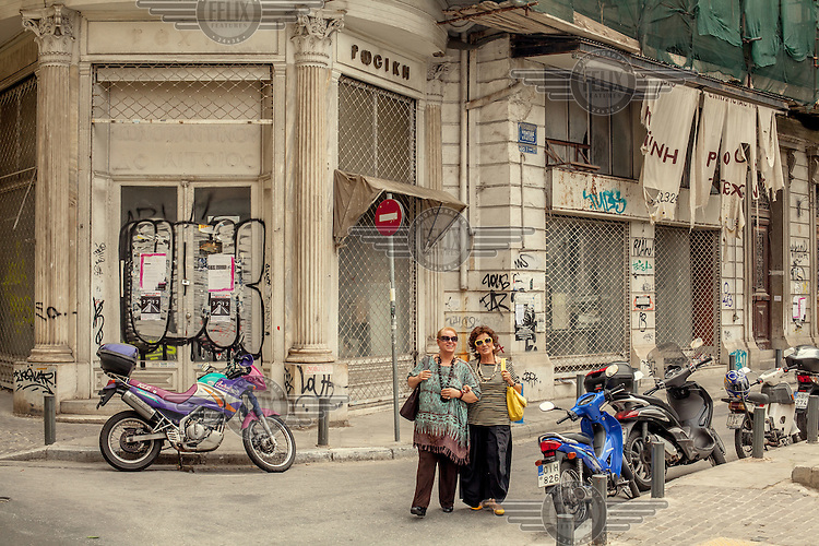Two smiling women walking on a street lined with closed down shops.