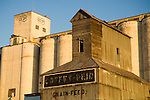 Old corrugated grain elevator against the backdrop of larger and newer concrete grain elevators