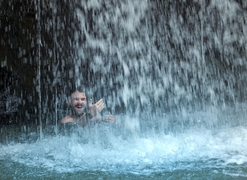 Swimmer behing Opai Pilau Falls. Hawaii, the big island.