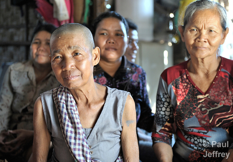Members of a women's self-help group in the Phnom Penh neighborhood of Sen Rikreay, including Shum Lorn, 65 (front), listen raptly as a Buddhist monk addresses the group. Many people in this community are infected or affected by HIV and AIDS, and Buddhist monks and other religious meet with them regularly to mediate and discuss their challenges.