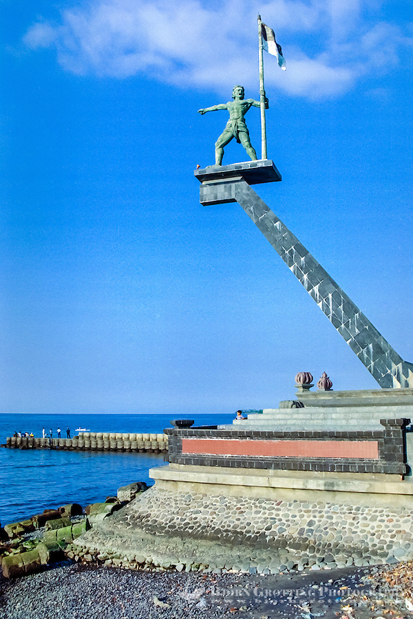 Bali, Buleleng, Singaraja. The statue of Ketut Merta with the Indonesian flag in Singaraja harbour.