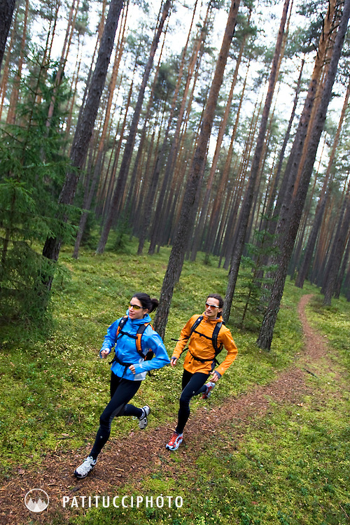Filippo Tosoratti and Amy Fountain trail running through a green forest outside of Brunico, Italy