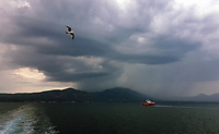WEATHER PICTURE<br /> A ferry boat is sees approaching the port of Eretria in Evia, as dark clouds and rain cover Dirfys Mountain on the same island in Greece. The country has been experiencing recent heatwaves. Thursday 27 July 2017