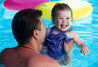 Father holding his delighted daughter in the pool.