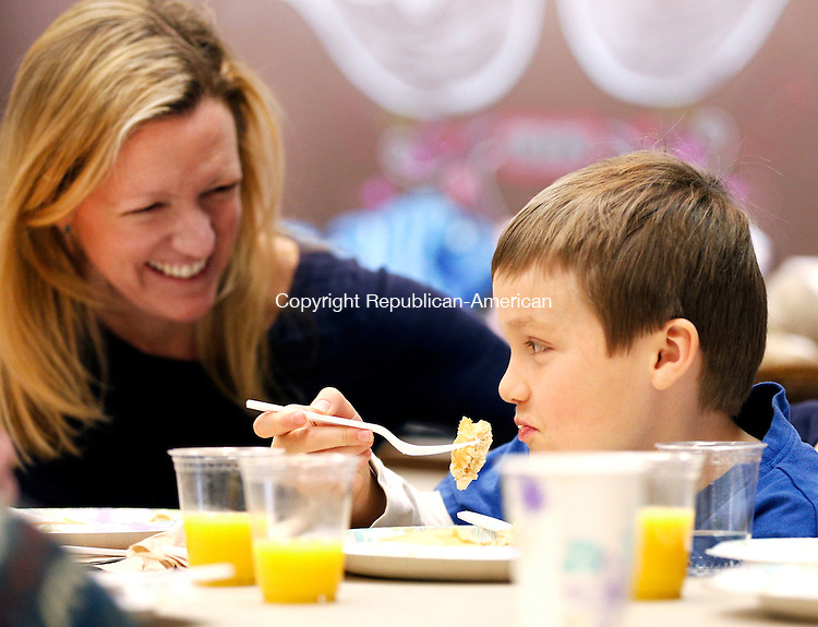 Woodbury, CT- 01 March 2015-030115CM03- Sara Lynn Leavenworth of Woodbury looks on and smiles as her son Hayden Renda, 8, enjoys a pancake breakfast at the Woodbury Emergency Services building in Woodbury on Sunday.  Also with the pair was Renda's younger brother, Justin Renda.  The Flanders Nature Center and Land Trust hosted its annual all-you-can-eat pancake breakfast, which featured Flanders' own maple syrup.  Christopher Massa Republican-American