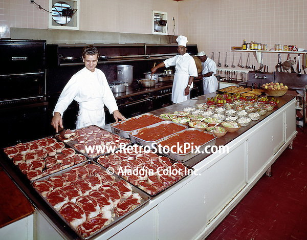 Three chefs preparing a large amount of food in kitchen