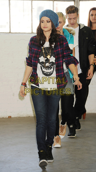 Selena Gomez .Announces new global partnership with iconic fashion brand Adidas Neo Label in Los Angeles, California, USA..November 20th, 2012.full length blue knitted beanie hat red lumberjack shirt check white shirt black skull print jeans denim trainers sneakers .CAP/ROT/TM.©Tony Michaels/Roth Stock/Capital Pictures