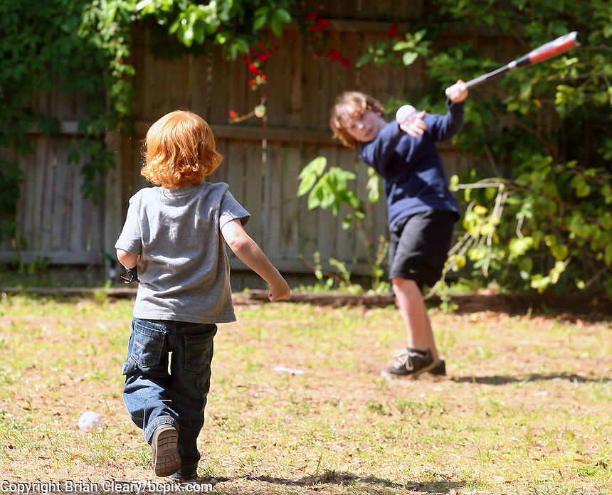 Two brothers play baseball in their backyard.  (Photo by Brian Cleary/www.bcpix.com)