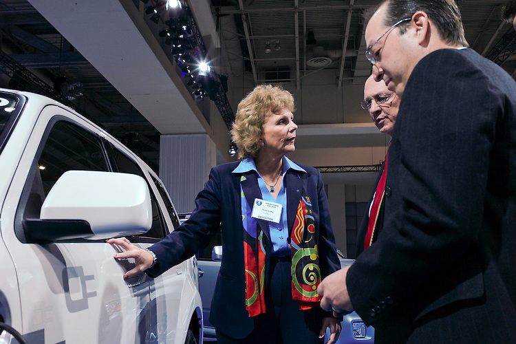 "WASHINGTON, DC - Jan. 22: Sue Cischke, senior vice president of Sustainability, Environment and Safety Engineering for Ford, shows off a plug-in Ford Escape to Assistant Energy Secretary Alexander ""Andy"" Karsner, far right, and former CIA Director R. James Woolsey during media day at the Washington Auto Show. At left is a hybrid Escape, at middle background is a flex fuel F150; at right is a plug in hybrid Escape. (Photo by Scott J. Ferrell/Congressional Quarterly)"